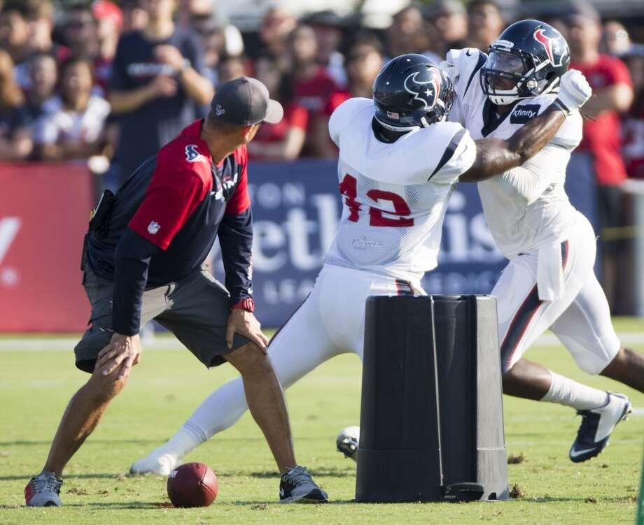 Texans running back Toben Opurum (42) blocks linebacker Justin Tuggle (57). Photo: Brett Coomer, Houston Chronicle