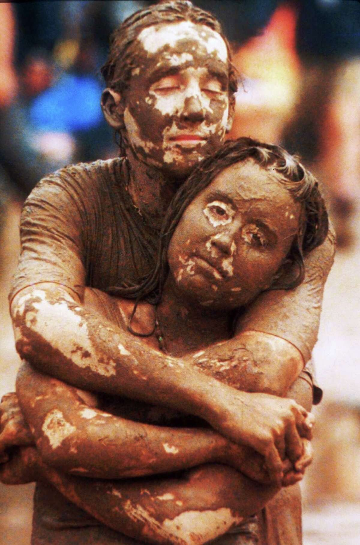 FILE--Standing on a muddy field in front of the stage, Kyle Keyser, 21, wraps his arms around Linda Latzlsberger, 18, as they listen to the music of Traffic during Woodstock '94 in Saugerties, N.Y., August 14, 1994. Both Keyser and Latzlsberger are from Baltimore.