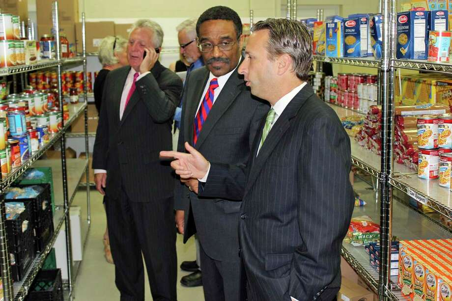 State Sen. Bob Duff (D-Norwalk), right, speaks with State Rep. Bruce Morris (D-Norwalk), center, as they visit the food pantry at Person-to-Person. Photo: Contributed Photo, Contributed / Darien News Contributed