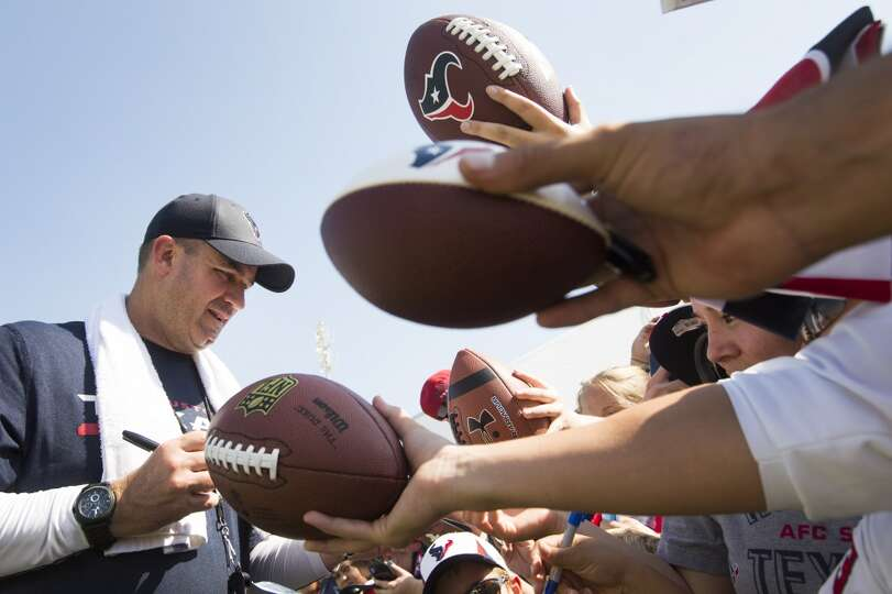 Texans head coach Bill O'Brien signs autographs.