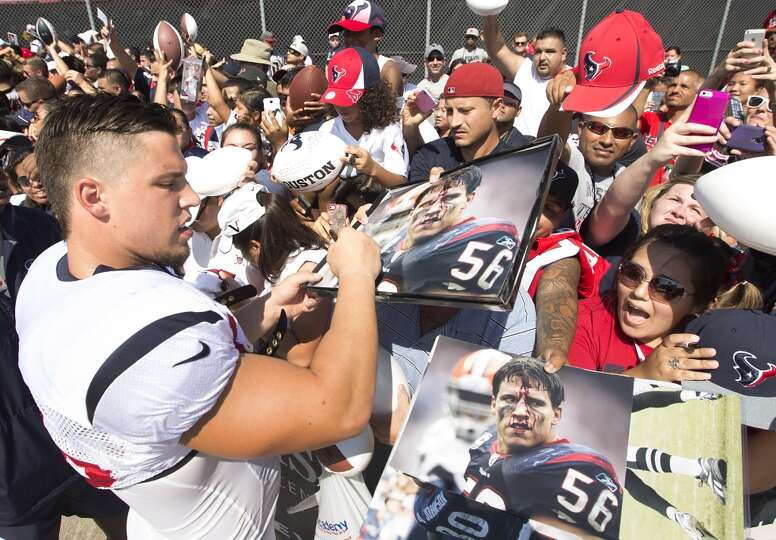 Texans inside linebacker Brian Cushing (56) signs autographs.