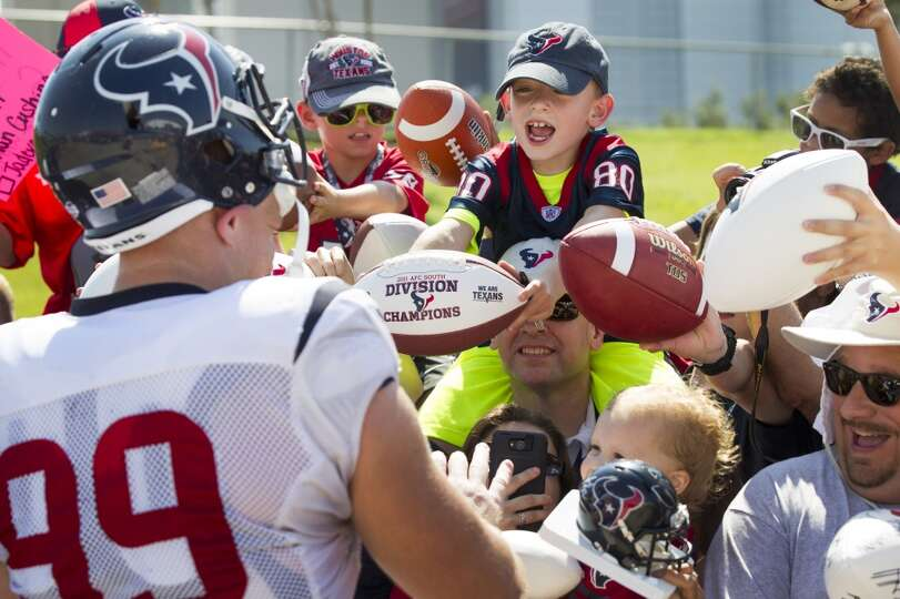 Texans defensive end J.J. Watt (99) signs autographs.