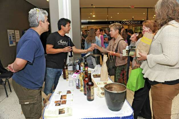 Carlos Seinario, left, and Ryan Ocasio of Brotherhood winery give out samples of their wine in the concourse of the Empire State Plaza on Wednesday, Aug. 13, 2014 in Albany, N.Y. The farmers' market, vendors from The New York State Food Festival and performers, including headliner Eddie Money, were brought inside due to a rainy forecast. (Lori Van Buren / Times Union) Photo: Lori Van Buren / 00027123A