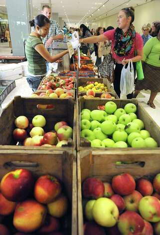 Ashley Ozemba, a UAlbany student, right, buys some fruit from Maria Guzman of Samascott Orchards at the farmers' market in the concourse of the Empire State Plaza on Wednesday, Aug. 13, 2014, in Albany, N.Y. The farmers' market, vendors from The New York State Food Festival and performers including headliner Eddie Money were brought inside due to a rainy forecast. (Lori Van Buren / Times Union) Photo: Lori Van Buren / 00027123A