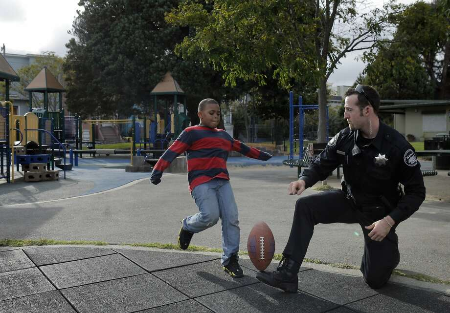 Damonta Robinson, 8, kicks a football held by Justin Cain, a private security officer with the Special Tactics and Response Security Patrol 