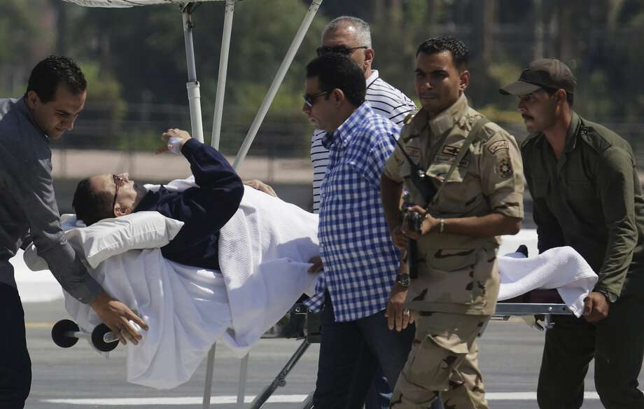 Egyptian medics and army personnel escort former Egyptian President Hosni Mubarak, 86, from a helicopter ambulance after landing at the Maadi Military Hospital, following his retrial in Cairo, Egypt, Wednesday, Aug. 13, 2014. Egypt's deposed President Mubarak on Wednesday denied that he ordered protesters killed during an uprising in 2011, in his first lengthy speech to a court as his year-old retrial draws to an end. (AP Photo/Amr Nabil) Photo: Amr Nabil, Associated Press