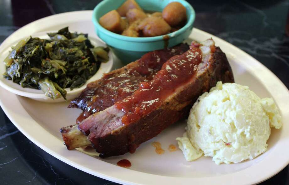 Da Cozy Spot serves barbecue plates with a choice of ribs (above), brisket and sausage. Side options include (clockwise from left) greens, yams and potato salad. Photo: Jennifer McInnis / San Antonio Express-News