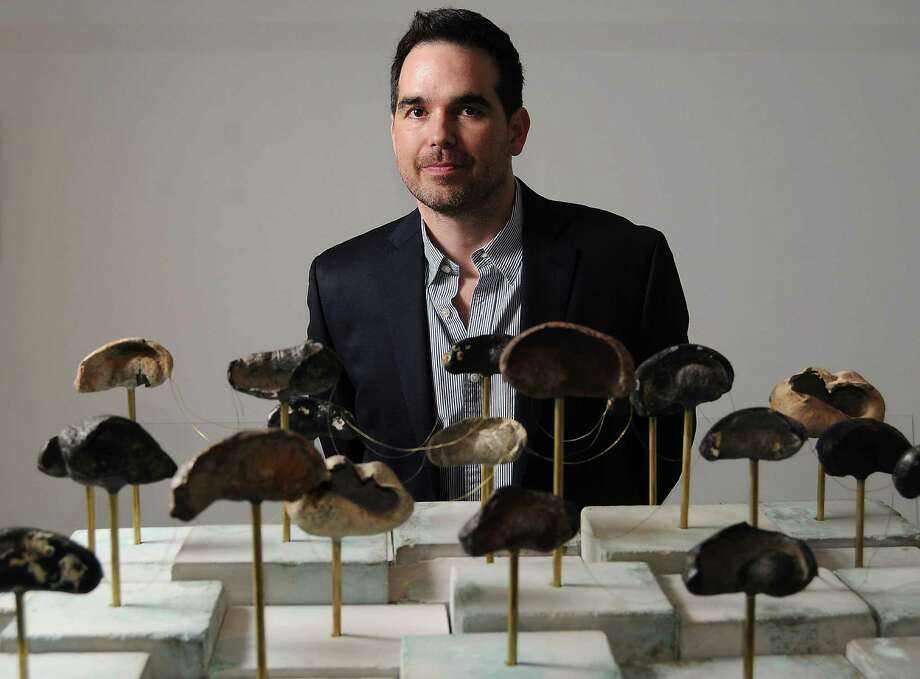 """Dario Robleto and the eardrums of prehistoric whales in """"Fossilhood Is Not Our Forever."""" Photo: Dave Rossman, Freelance / © 2014 Dave Rossman"""