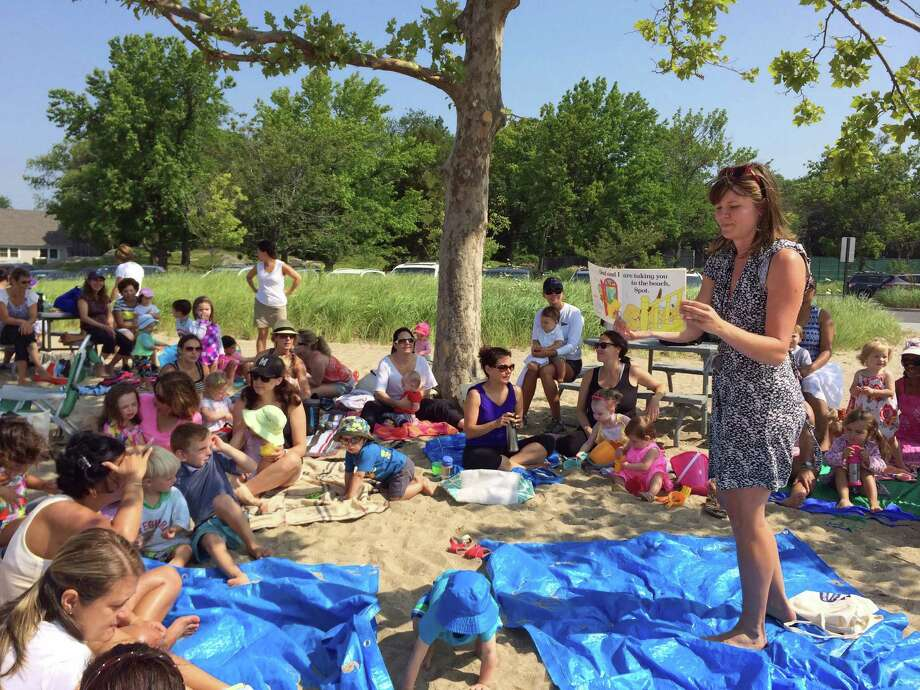 Lisa Nowlain will spend the next two years working at the Darien Library as the Harold W. McGraw Jr. Fellow. Above, she reads to children and their families during a recent story time event at Weed Beach. Photo: Contributed Photo, Contributed / Darien News Contributed