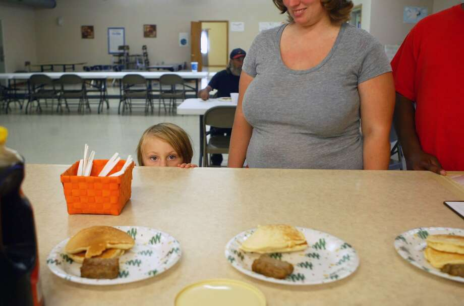 Pass the syrup: Three-year-old Emma Robertson peers over the counter at a pancakes-and-sausage breakfast served by the Spirit of Faith soup kitchen in Jacksonville, Fla. Photo: Bre Linstromberg Copper, Associated Press