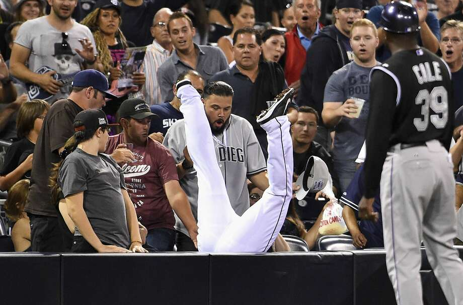Half Nelson:San Diego's Chris Nelson partially disappears into the seats while chasing a foul ball during the Rockies-Padres game at Petco Park. And, yes, he made the catch. Photo: Denis Poroy, Getty Images