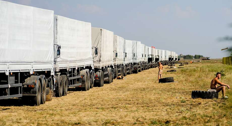 "Trucks of Russian humanitarian convoy wait at the location outside Voronezh some 400 km outside Moscow on August 13, 2014. A massive Russian aid convoy rumbled towards Ukraine's border on August 13 as Kiev vowed to block what it feared could be a ""Trojan horse"" bringing military assistance to pro-Kremlin rebels fighting a bloody insurgency in the east. Russian television images showed a line of nearly 300 lorries moving through the countryside, covered with white tarpaulin and stretching over almost three kilometres (two miles).  AFP PHOTO / VLADIMIR BARYSHEVVLADIMIR BARYSHEV/AFP/Getty Images Photo: Vladimir Baryshev, AFP/Getty Images"
