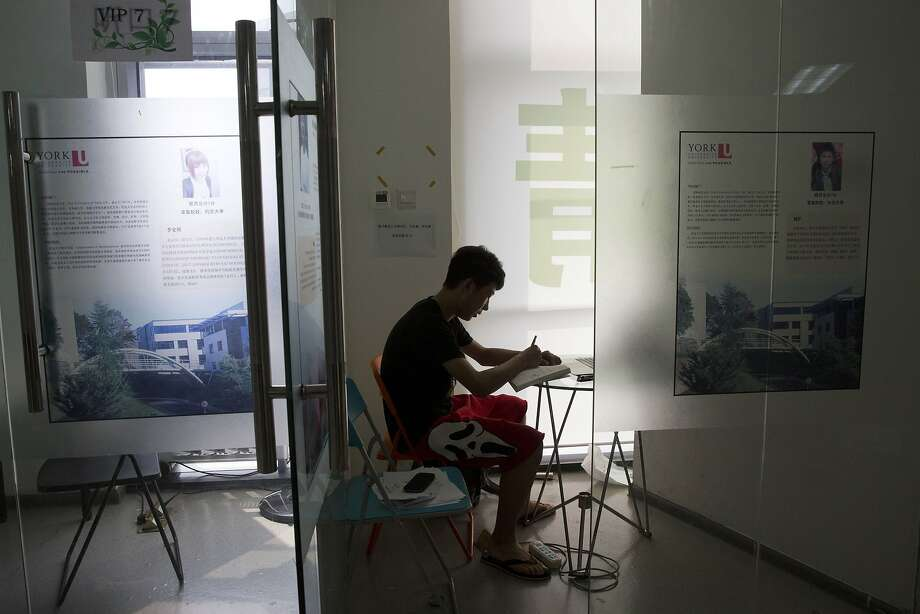 Zhang Kaisheng, 16, studies at Focus Education, a tutoring and consulting agency in Beijing, where ads for overseas schools are seen on the walls. Photo: Ng Han Guan, Associated Press
