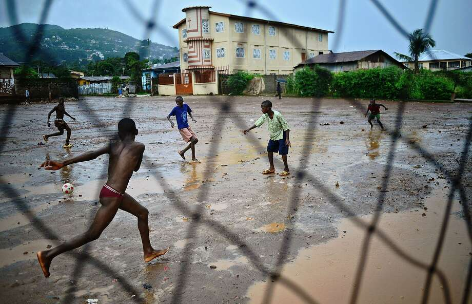 Young boys play football in the rain in Freetown on August 13, 2014. The World Health Organisation (WHO) revealed that the latest death toll from the Ebola virus in Guinea, Sierra Leone, Liberia and Nigeria had claimed more than1000  lives. Health Organisations are looking into the possible use of experimental drugs to combat the latest outbreak in West Africa which is also the largest ebola outbreak in history. AFP PHOTO/Carl de SouzaCARL DE SOUZA/AFP/Getty Images Photo: Carl De Souza, AFP/Getty Images