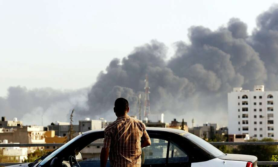 A man stands by his car as black smoke billows across the sky after a petrol depot was set ablaze during clashes between rival militias near Tripoli's international airport, on the outskirts of the capital, on August 13, 2014. Since mid-July, the country has been rocked by deadly inter-militia fighting for control of key facilities including Tripoli's international airport. Benghazi in the east, Libya's second city, has also seen battles between Islamists and the forces of a renegade general. AFP PHOTO/STR-/AFP/Getty Images Photo: -, AFP/Getty Images