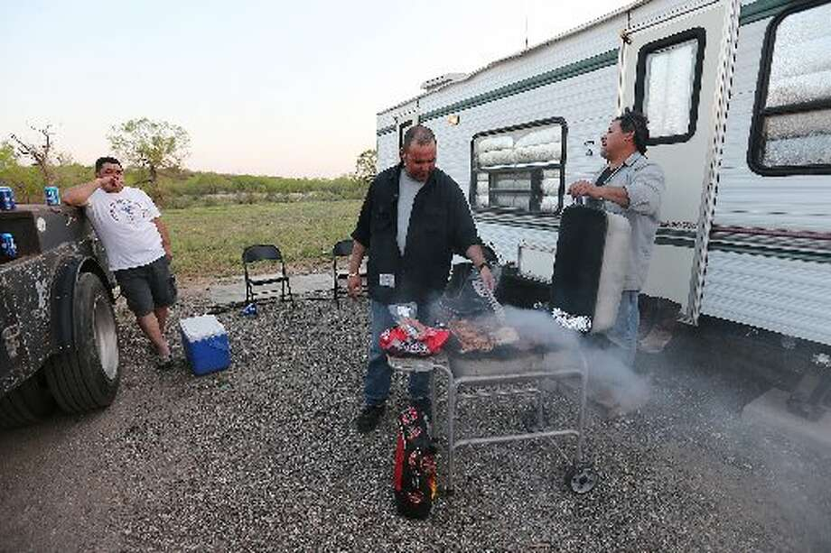After the end of the workday, Rio Grande Valley friends gather for dinner at the Boss RV Park in Tilden, Texas on Wednesday, April 2, 2014. From left, Gerardo Garcia, 44, of Edinburg, Gustavo Gonzalez, 39, of Hidalgo and Raul Serna, 48, of Mission, work as welders and welder's helpers in the Eagle Ford Shale Play. (Jerry Lara/ San Antonio Express-News)