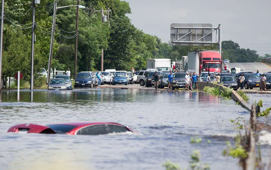 People look on as a car remains submerged on Sunrise Highway at Route 111 after record-setting heavy rains and flash flooding in Islip, N.Y. Photo: Andrew Theodorakis, Getty Images