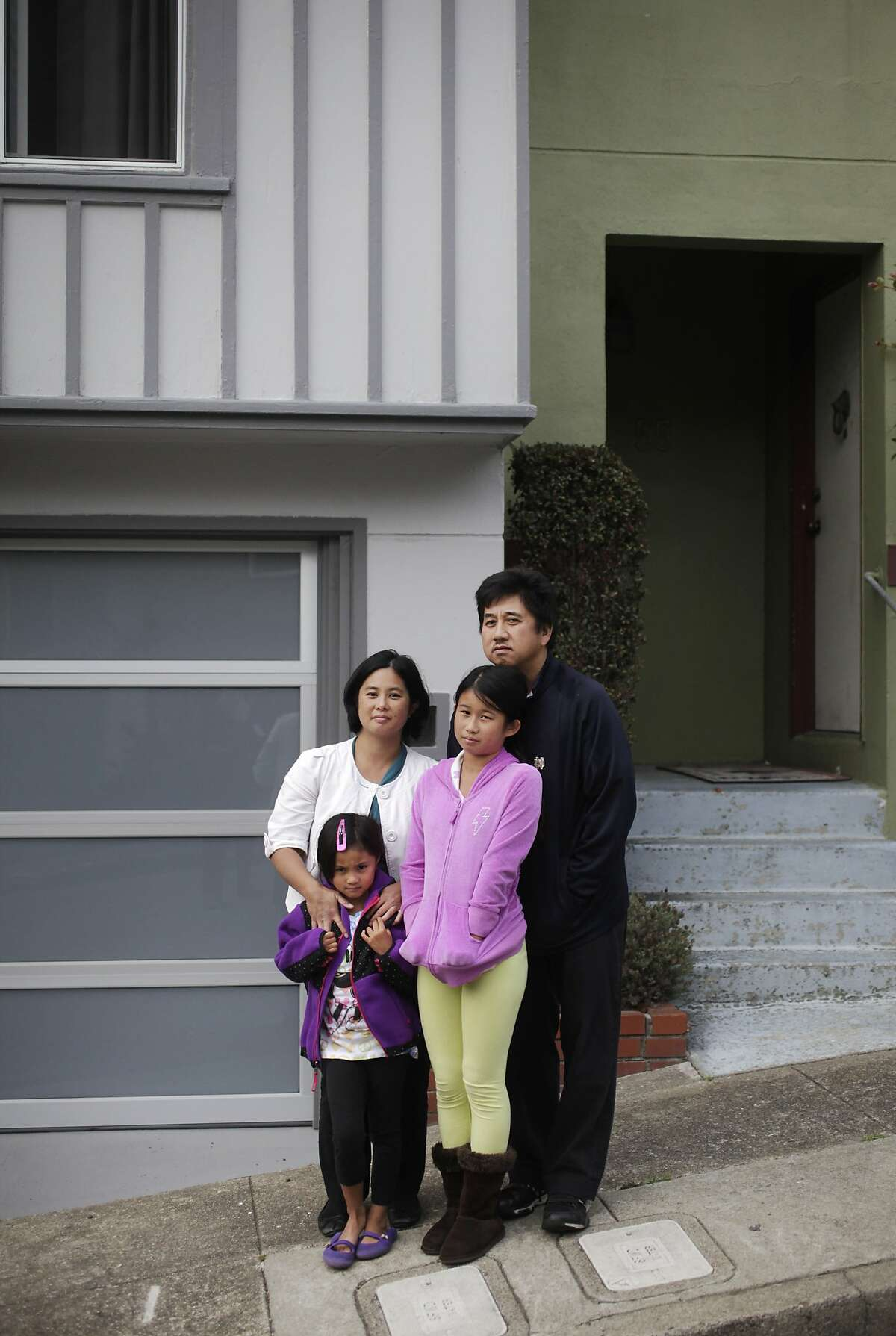 Alcan family members Kathy and Phil stand for a portrait with their daughters Stephanie, 7, and Samantha, 10, in front of their home, right, which now shares a wall with an Airbnb rental home, left, August 6, 2014 in a Twin Peaks cul-de-sac in San Francisco, Calif. A group of neighbors who live on the street are upset about an increase of homes that are being rented to Airbnb. Of 34 homes on the street, three are now Airbnb, according to the neighbors.