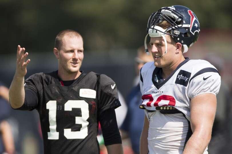 Atlanta Falcons quarterback T.J. Yates (13) talks to Texans defensive end J.J. Watt (99) after pract