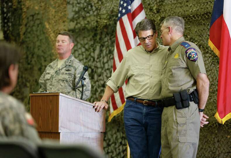 Texas Gov. Rick Perry confers with Department of Public Safety Director Steven McCraw Wednesday Aug.