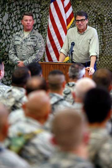 Texas Gov. Rick Perry, right, flanked by Major Gen. John F. Nichols, left, talks Wednesday Aug. 13,