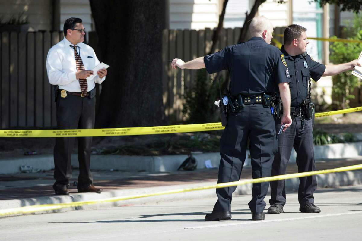 Law enforcement officers investigate the scene of an officer-involved shooting near the intersection of Airline and Aldine-Bender Wednesday, Aug. 13, 2014, in Houston. One officer and one suspect were transported to area hospitals following the shooting.