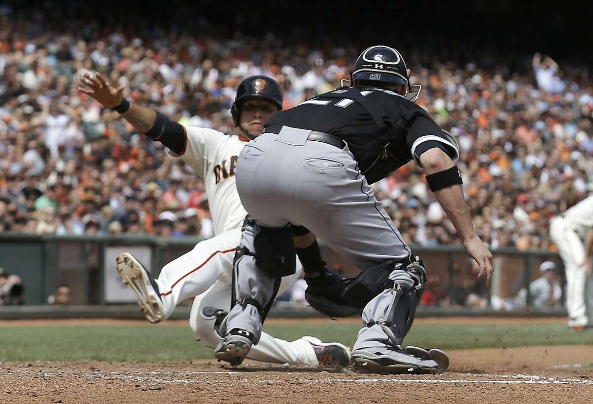 Gregor Blanco (left) was tagged out by Tyler Flowers trying to score on Joe Panik's groundball. He was then called safe because Flowers impeded his path, a ruling Chicago manager Robin Ventura, below, disputed.