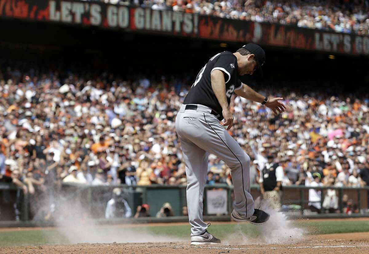 Chicago manager Robin Ventura shows his disgust with the overturned play in the seventh by kicking dirt on home plate.