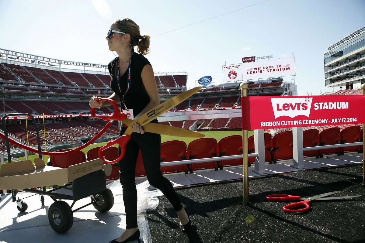 Mahelly Ferreira carries oversize scissors before the ribbon-cutting ceremony that officially opened the 49ers' 68,500-seat, $1.31 billion Levi's Stadium in Santa Clara on July 17.