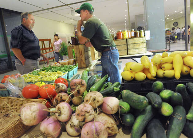 Howard Katz, left, talks to Loren Conbeer of Conbeer's farm in Fonda during a farmers market in the concourse of the Empire State Plaza on Wednesday, Aug. 13, 2014 in Albany, N.Y. Katz was looking for local farms to supply vegetables for a new restaurant he is opening soon called Terra. The restaurant features international cuisine featuring vegan, vegetarian, pescetarian and gluten free selections. The farmers market, vendors from The New York State Food Festival and performers including headliner Eddie Money were brought inside due to a rainy forecast. (Lori Van Buren / Times Union) Photo: Lori Van Buren, Albany Times Union / 00027123A