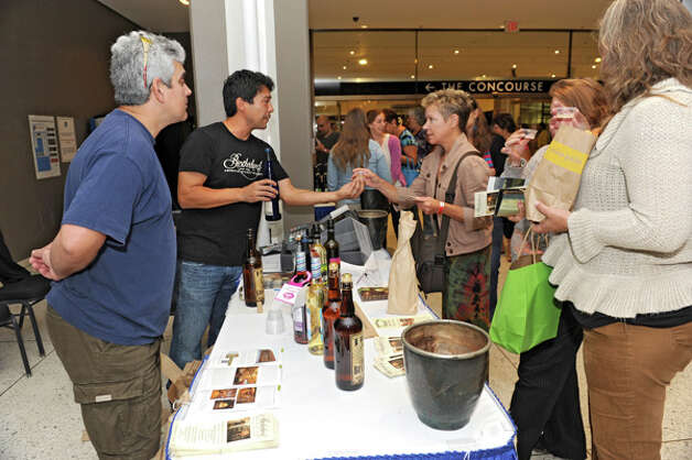 Carlos Seinario, left, and Ryan Ocasio of Brotherhood winery give out samples of their wine in the concourse of the Empire State Plaza on Wednesday, Aug. 13, 2014 in Albany, N.Y. The farmers market, vendors from The New York State Food Festival and performers including headliner Eddie Money were brought inside due to a rainy forecast. (Lori Van Buren / Times Union) Photo: Lori Van Buren, Albany Times Union / 00027123A