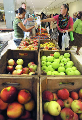 Ashley Ozemba, a UAlbany student, right, buys some fruit from Maria Guzman of Samascott Orchards at the farmers market in the concourse of the Empire State Plaza on Wednesday, Aug. 13, 2014 in Albany, N.Y. The farmers market, vendors from The New York State Food Festival and performers including headliner Eddie Money were brought inside due to a rainy forecast. (Lori Van Buren / Times Union) Photo: Lori Van Buren, Albany Times Union / 00027123A