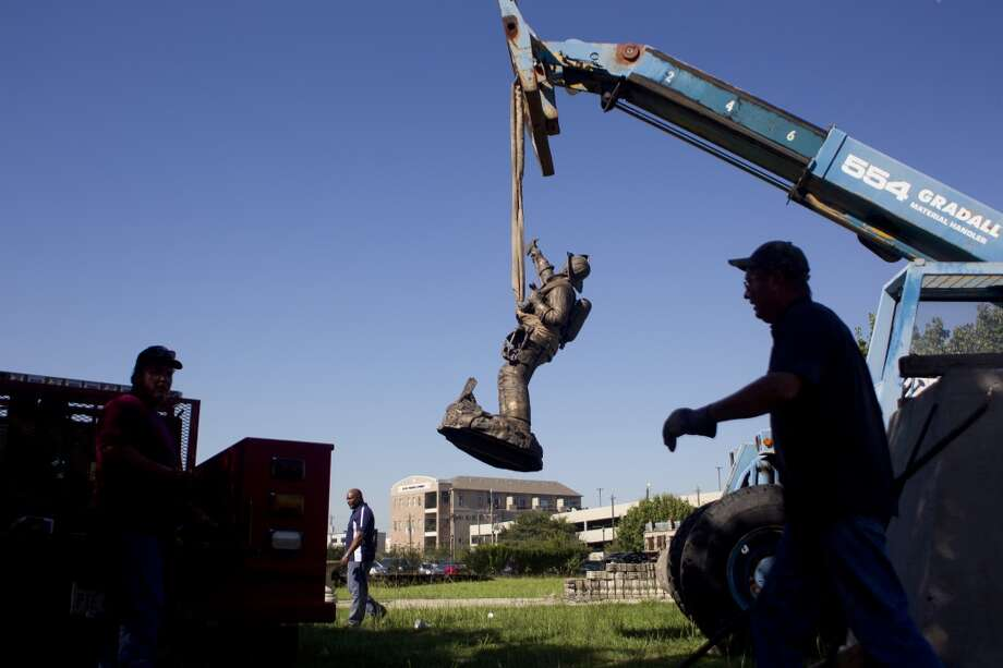 Clayton Barefield, right, with Admiral Transfer and Rigging Inc., walks past the bronze statue titled 'In the Line of Fire' owned by the Houston Fire Museum and created by local sculptor Edd Hayes is moved from the corner of Hadley and Main Streets to a temporary home at the museum Wednesday, Sept. 25, 2013, in Houston. The statue will be kept at the museum until a new home is found for it. Hayes was inspired to create the statue after the terrorist attack on the World Trade Center on Sept. 11, 2001. Seven firefighters posed for the statue.  ( Johnny Hanson / Houston Chronicle ) Photo: Johnny Hanson, Houston Chronicle