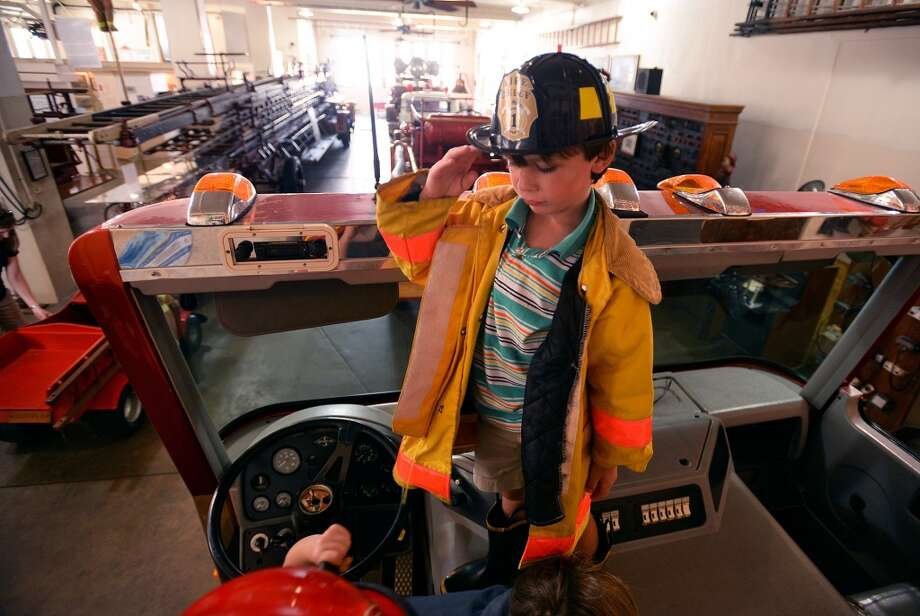 Andrew Huggins salutes atop the faux firetruck at the Beaumont Fire Museum on Friday. The museum offered hands on activities and taught children about the different jobs at the fire department.  Photo taken Friday, July 25, 2014 Guiseppe Barranco/@spotnewsshooter Photo: Guiseppe Barranco