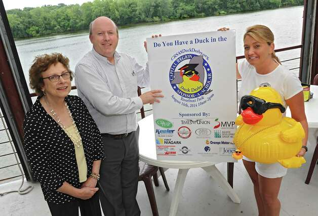 From left, Julie Liss, community development coordinator for Capital Region Sponsor-A-Scholar Inc., William Corbett, Sr., President of Capital Region Sponsor-A-Scholar Inc. and Cheri West, owner of Riverfront Bar and Grill stand with a Duck Derby poster at Cheri's restaurant on the river on Tuesday, Aug. 12, 2014 in Albany, N.Y. Together they are organizing the upcoming Capital Region Sponsor-A-Scholar Duck Derby from 10 a.m. to 2 p.m. Saturday. (Lori Van Buren / Times Union) Photo: Lori Van Buren / 00028109A