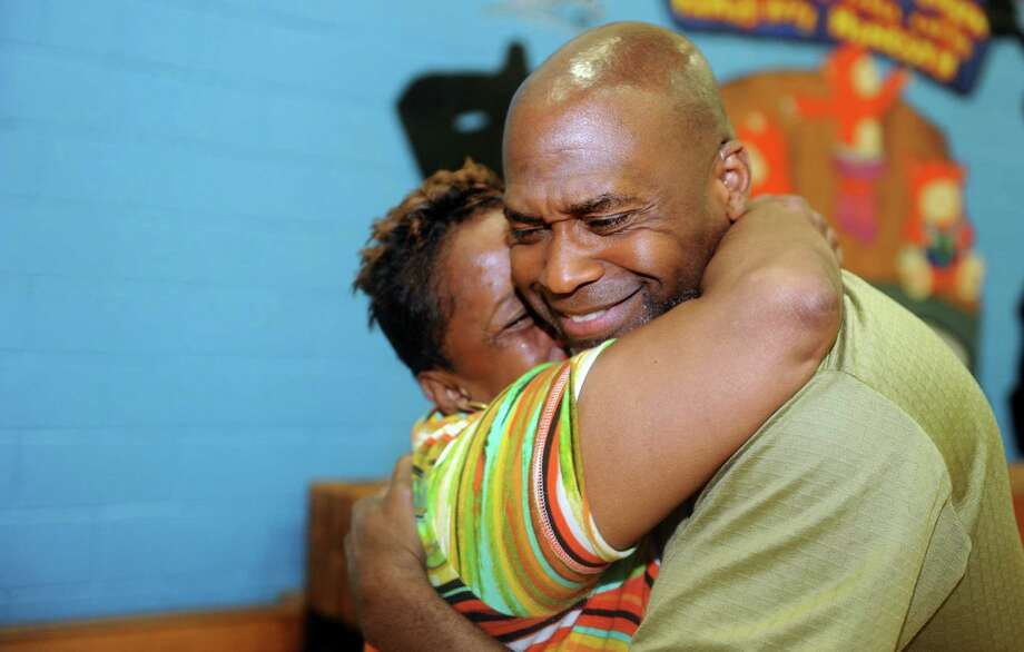 Andre Baker hugs Brenda Jernigan, a member of his campaign, as results are tallied at Dunbar School in Bridgeport, Conn., Tuesday, Aug. 12, 2014. Baker defeated former state Sen. Ernest E. Newton in a primary race for the 124th state House District seat. Photo: Autumn Driscoll / Connecticut Post