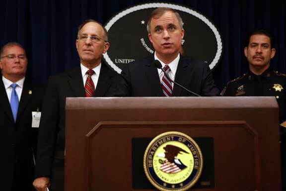 Marshall Miller of the Department of Justice, at lectern, with other officials including Harris County Sheriff Adrian Garcia, right, discuss the gang cases.
