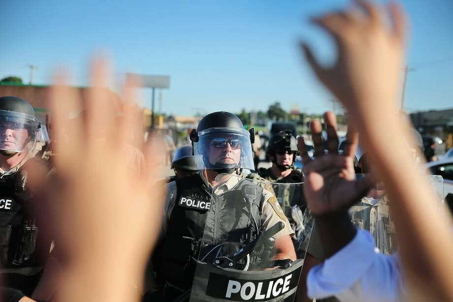 A child, who was being held by her mother who was protesting the shooting death of teenager Michael Brown, holds up her hands after police ordered them off the street by  on August 13, 2014 in Ferguson, Missouri. Brown was shot and killed by a Ferguson police officer on Saturday. Ferguson, a St. Louis suburb, has experienced three days of violent protests since the killing. Photo: Scott Olson, Getty Images