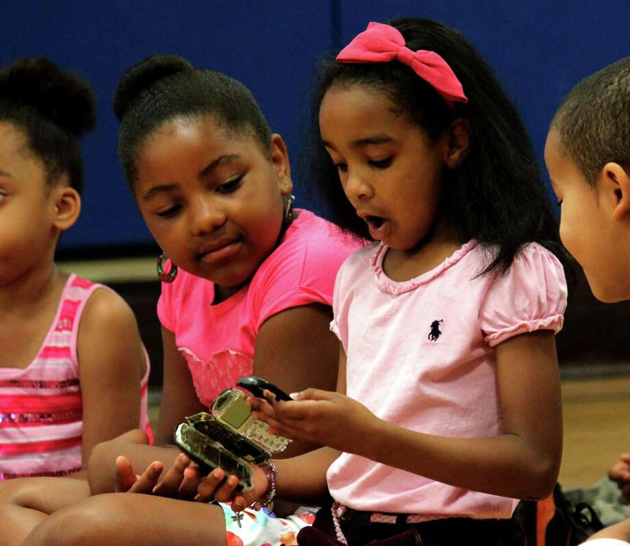Elise Pendleton, 8, left, and Kalia Cherry, 6, both of Albany, study a disassembled cellphone during GlobalFoundries Engineers Day at Trinity Alliance on Wednesday, August 13, 2014, in Albany N.Y. Engineers from GlobalFoundries conducted interactive and educational science, technology, engineering and mathmatics experiments with the summer camp children. (Selby Smith/Special to the Times Union) Photo: Selby Smith / 00028144A