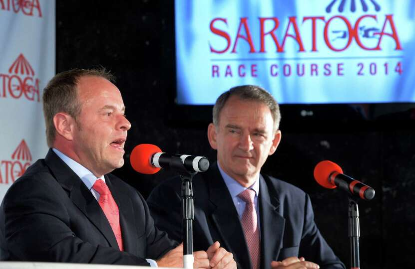 Larry Collmus, left, speaks after being named as the new track announcer by NYRA CEO Chris Kay, righ
