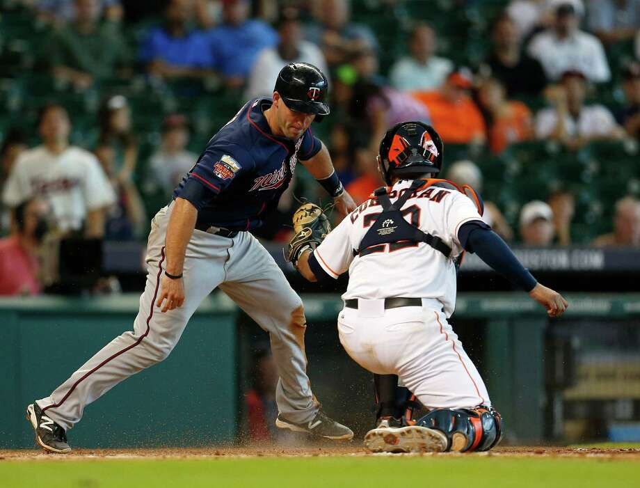 Twins catcher Eric Fryer, left, is tagged out by Astros catcher Carlos Corporan after trying to score from third on Brian Dozier's ninth-inning grounder to short. Photo: Karen Warren, Staff / © 2014 Houston Chronicle