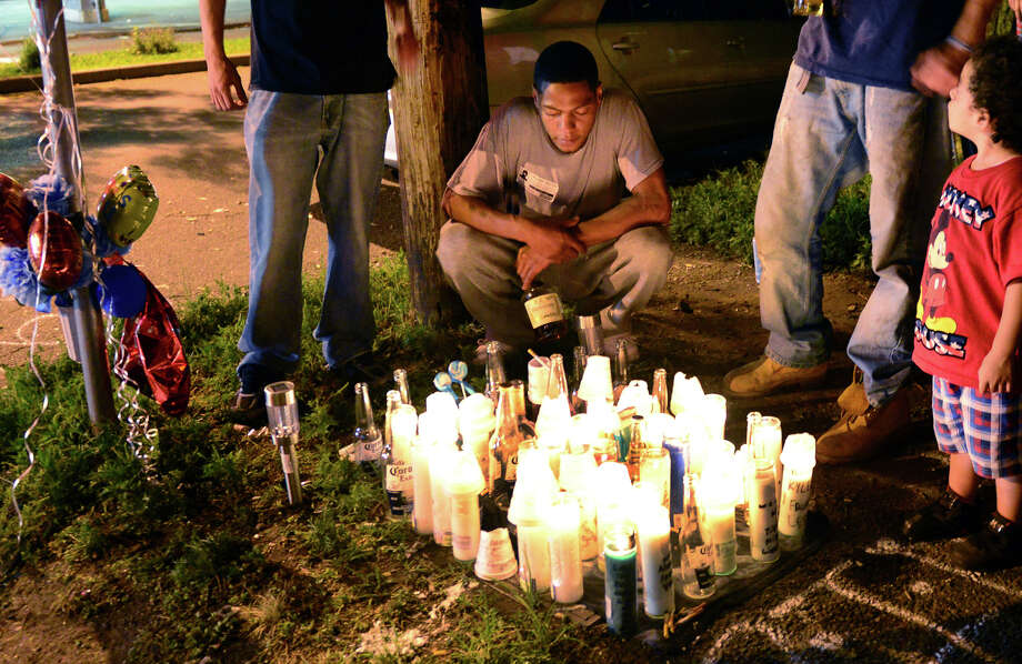Carlos Soler, brother of hit-and-run victim Kyle Williams, pays tribute to him at a memorial at the coner of Park Avenue and Vine Street in Bridgeport, Conn. on Wednesday, August 13, 2014. Williams was hit at the intersection on Saturday and died last night. Photo: Christian Abraham / Connecticut Post