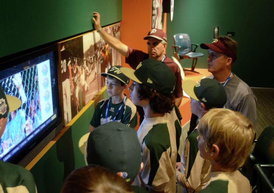 Manager Don Smith, right, and his Pearland East team watch highlights of the 2010 Little League World Series on Tuesday. Photo: Ralph Wilson / Houston Chronicle