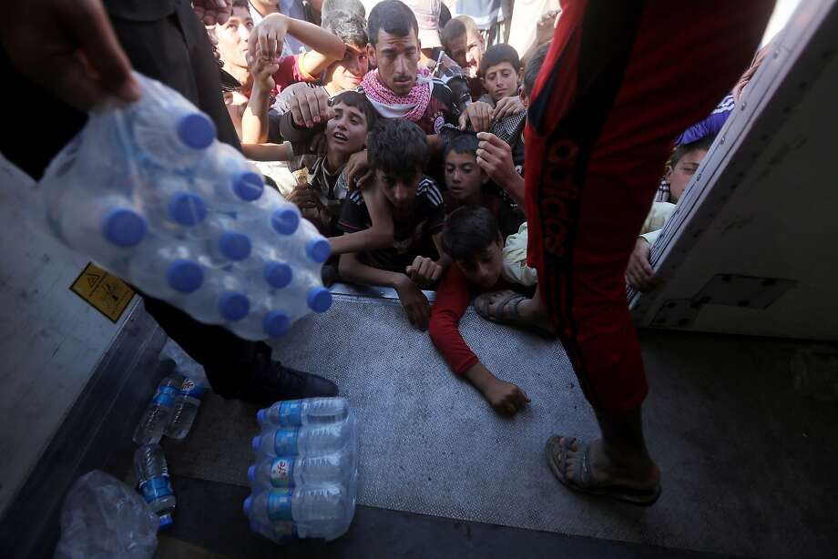 Displaced Iraqi Yazidis, who fled a jihadist onslaught on Sinjar, gather to collect bottles of water at the Bajid Kandala camp in Kurdistan's western Dohuk province, on August 13, 2014. Scores of young men and children held a protest demanding more aid at the Bajid Kandala camp that is hosting thousands of desperate Iraqi Yazidis. AFP PHOTO/AHMAD AL-RUBAYEAHMAD AL-RUBAYE/AFP/Getty Images Photo: Ahmad Al-rubaye, AFP/Getty Images
