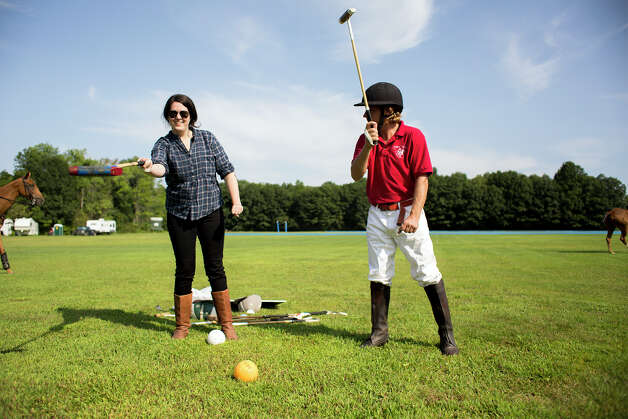 Polo player Mario Dino, right, teaches Deanna Fox how to strike the polo ball Friday morning, Aug. 8, 2014, at the Saratoga Polo Association grounds in Saratoga Springs, N.Y. (Tom Brenner/ Special to the Times Union) Photo: Tom Brenner / ©Tom Brenner/ Albany Times Union