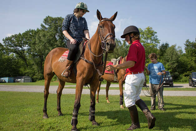 Mario Dino holds onto the reigns while Deanna Fox mounts the horse on Friday morning, Aug. 8, 2014, at the Saratoga Polo Association grounds in Saratoga Springs, N.Y. (Tom Brenner/ Special to the Times Union) Photo: Tom Brenner / ©Tom Brenner/ Albany Times Union