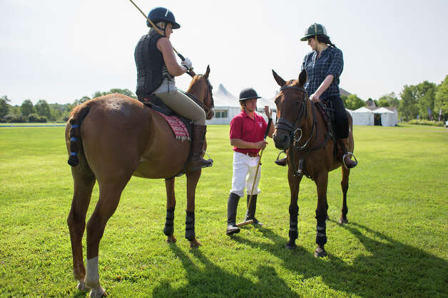 Polo player Mario Dino, center, teaches Deanna Fox, right, how to strike the polo ball Friday morning, Aug. 8, 2014, at the Saratoga Polo Association grounds in Saratoga Springs, N.Y. (Tom Brenner/ Special to the Times Union) Photo: Tom Brenner / ©Tom Brenner/ Albany Times Union