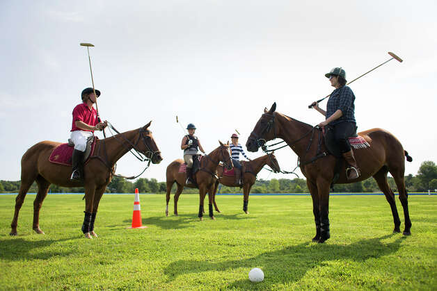 Polo player Mario Dino, left, teaches Deanna Fox, right, how the game of polo is played Friday morning, Aug. 8, 2014, at the Saratoga Polo Association grounds in Saratoga Springs, N.Y. (Tom Brenner/ Special to the Times Union) Photo: Tom Brenner / ©Tom Brenner/ Albany Times Union