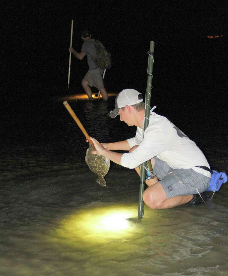 As Wyatt Lang hunts in the background, Dylan Motley strings a flounder he gigged after using a portable, submersible battery-powered light to locate it. Photo: Picasa