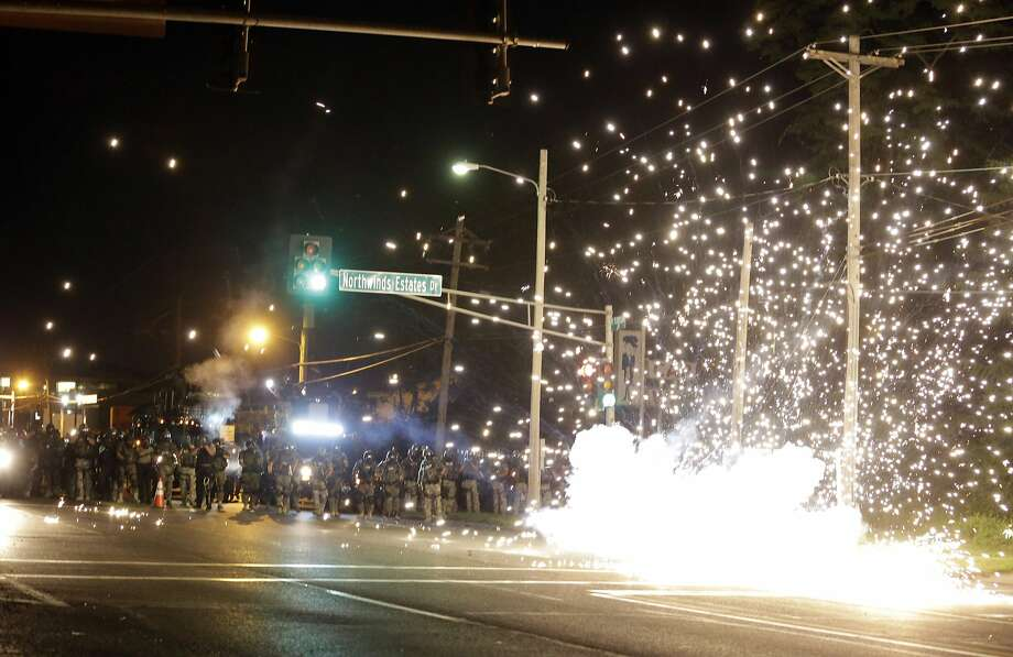 A device deployed by police goes off in the street as police and protesters clash Wednesday, Aug. 13, 2014, in Ferguson, Mo. Authorities in the St. Louis suburb where an unarmed black teen was shot and killed by a police officer have used tear gas to try to disperse protesters after flaming projectiles were thrown from the crowd. Photo: Jeff Roberson, Associated Press